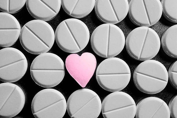 heart shaped pill amongst standard meds - prescription meds stock pictures, royalty-free photos & images