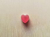 heart shaped pink candy on wooden clear background