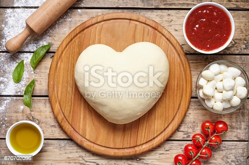 1136817041 istock photo Heart shaped pizza cooking ingredients. Dough, mozzarella, tomatoes, basil, olive oil, spices. Work with the dough. Top view. Flat lay. Traditional italian pizza margherita. 670702096