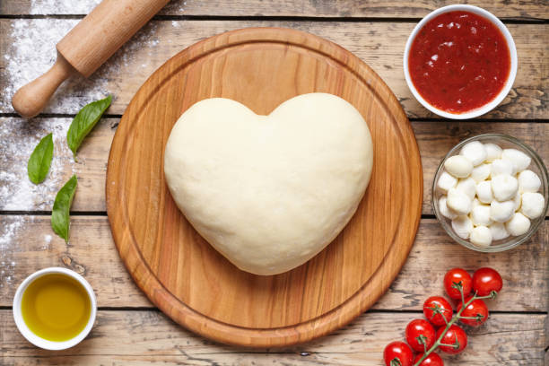 Heart shaped pizza cooking ingredients. Dough, mozzarella, tomatoes, basil, olive oil, spices. Work with the dough. Top view. Flat lay. Traditional italian pizza margherita. stock photo