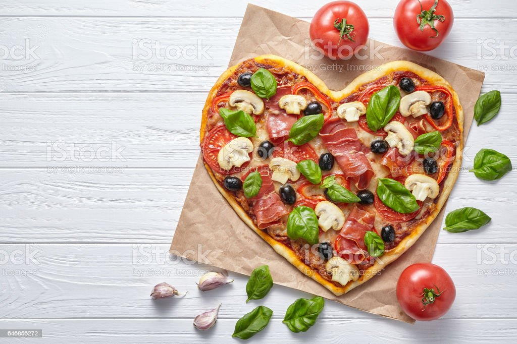 Heart shaped pizza delicious love concept Valentine's Day design romantic restaurant dinner Heart shaped pizza delicious love concept Valentine's Day design romantic restaurant dinner Italian food. Olives, prosciutto, champignons, tomatoes and mozzarella meal served on white wooden table Backgrounds Stock Photo
