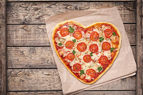 Heart shaped pizza margherita with tomatoes and mozzarella for Valentines stock photo