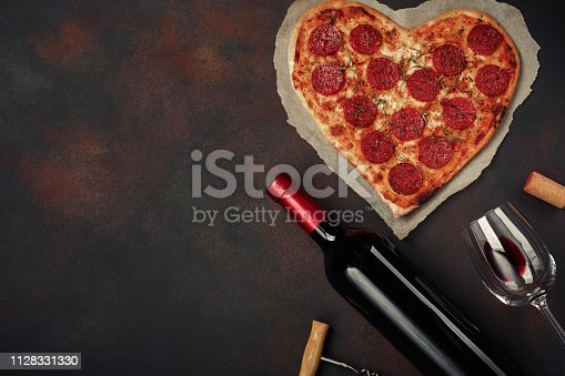 istock Heart shaped pizza with mozzarella, sausagered with a bottle of wine and wineglas on rusty background. 1128331330