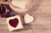 High angle view of raspberry jam jar and heart shaped jam on slice of bread placed on the left corner with one spoon beside the jar