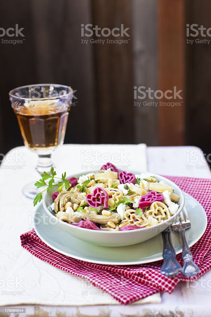 Heart shaped red and white pasta with artichokes royalty-free stock photo