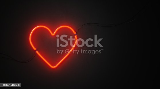 Heart shaped red neon light on black wall. Horizontal composition with copy space. Great use for Valentines Day concepts.