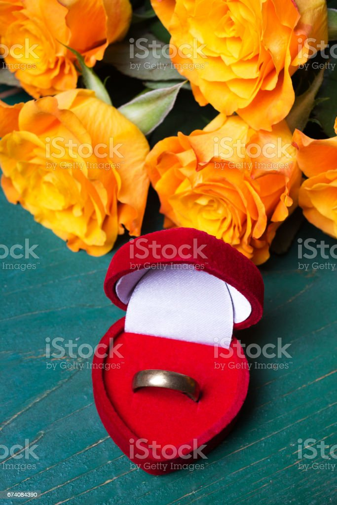 Heart shaped ring box and bouquet of roses on blue background foto de stock royalty-free