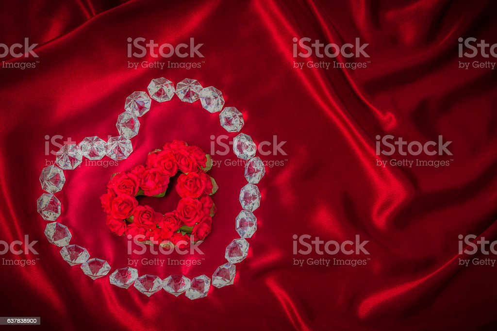 Heart shaped Roses outlined with diamonds on red satin (P) stock photo