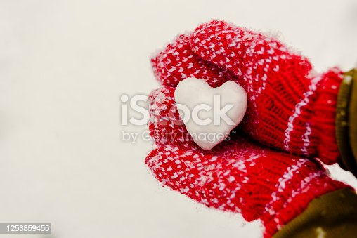 Heart shaped snowball in hands in red knitted mittens