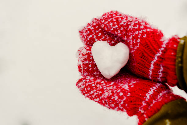 Heart shaped snowball in hands in knitted mittens
