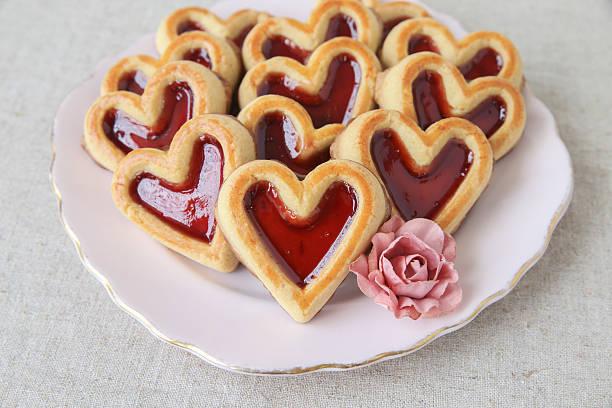 herzförmiger erdbeere marmelade und schokolade cookies zum valentinstag - spitzenkekse stock-fotos und bilder
