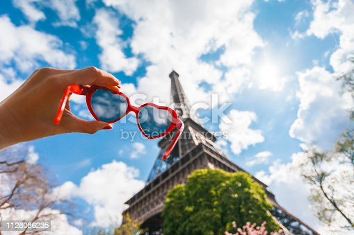 Heart shaped sunglasses in a women hand against Eiffel Tower and blue sky  (Paris France)