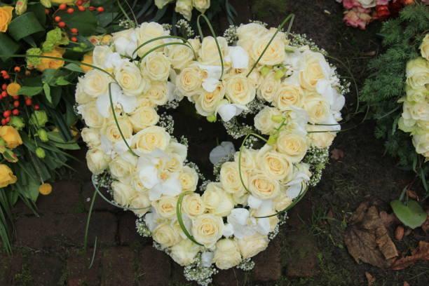 heart shaped sympathy wreath near a tree - funerale foto e immagini stock