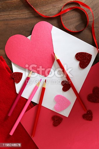 A red construction paper cut heart with copy-space is sitting in a white envelope surrounded by colored pencils, ribbon, and Valentine's day art supplies on a wood table.