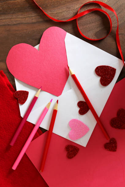 Heart Shaped Valentine's Day Card in Envelope on Table with Art Supplies stock photo