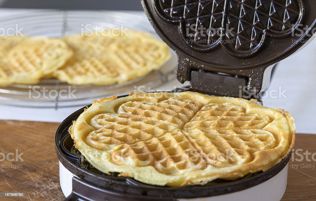 Heart shaped waffle maker in use on a wood countertop stock photo