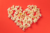 istock Heart shaped white fluffy popcorn on red background 1065099002