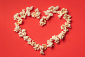 istock Heart shaped white fluffy popcorn on red background with empty space for text 1065101240