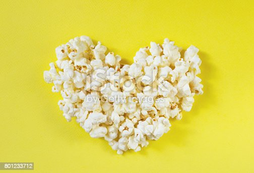 istock Heart shaped white fluffy popcorn on yellow 801233712