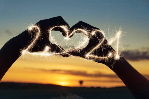 Heart silhouette at sunset with sparkler 2021 stock photo