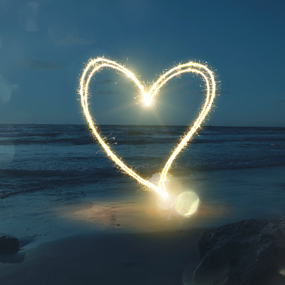 Sparkles in heart shape over sand at the beach