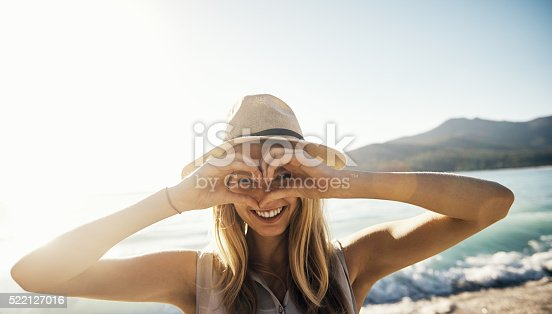 Shot of a young woman making a heart shaped gesture with his hands on a day at the beach