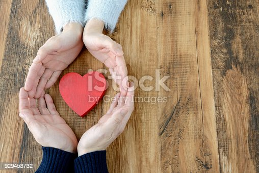 Heart surrounded by man and woman's hand