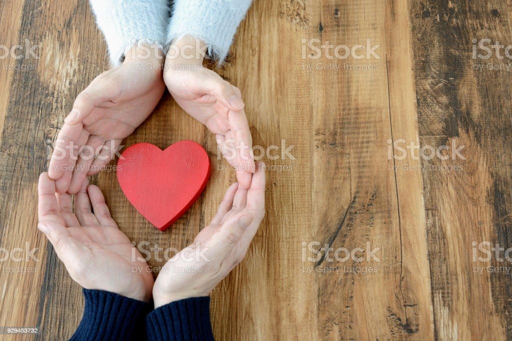 Corazón rodeado por mano de hombre y de mujer - foto de stock