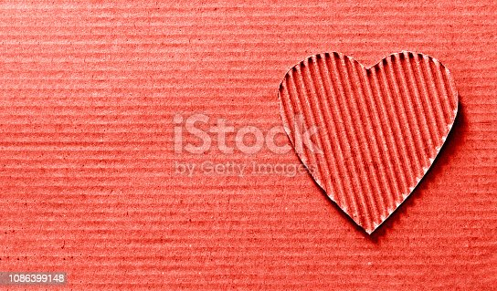 heart symbol carved out of corrugated cardboard. Copy space, top view. trendy color 2019  year Living Coral