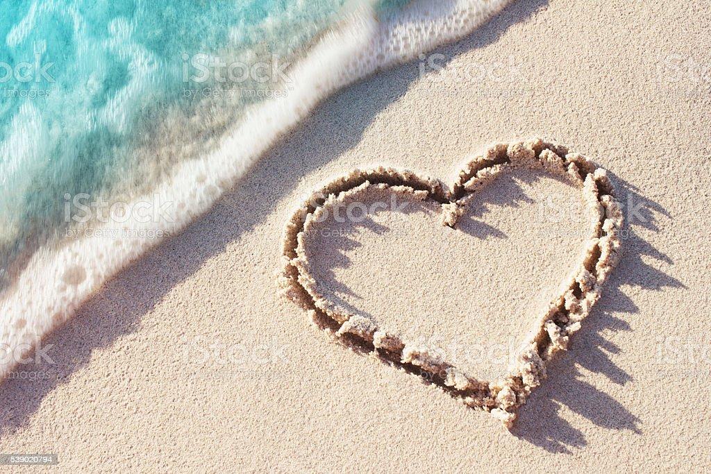 Heart symbol handwritten on a tropical beach stock photo