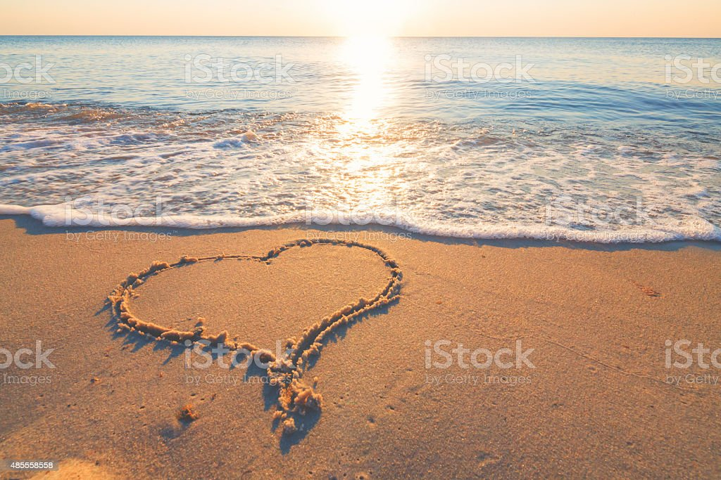 Heart symbol in the sand by the ocean stock photo