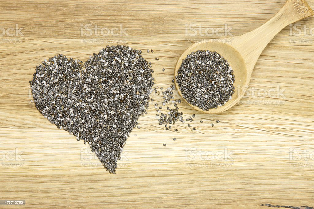heart symbol made of black chia seeds and spoon stock photo
