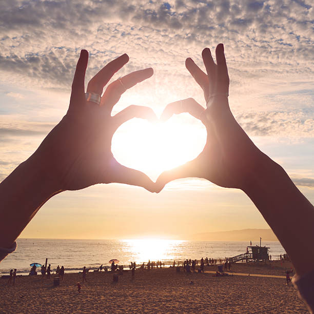 Heart symbol made with hands on the beach stock photo