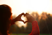 Young women making heart symbol in front of sunlight.