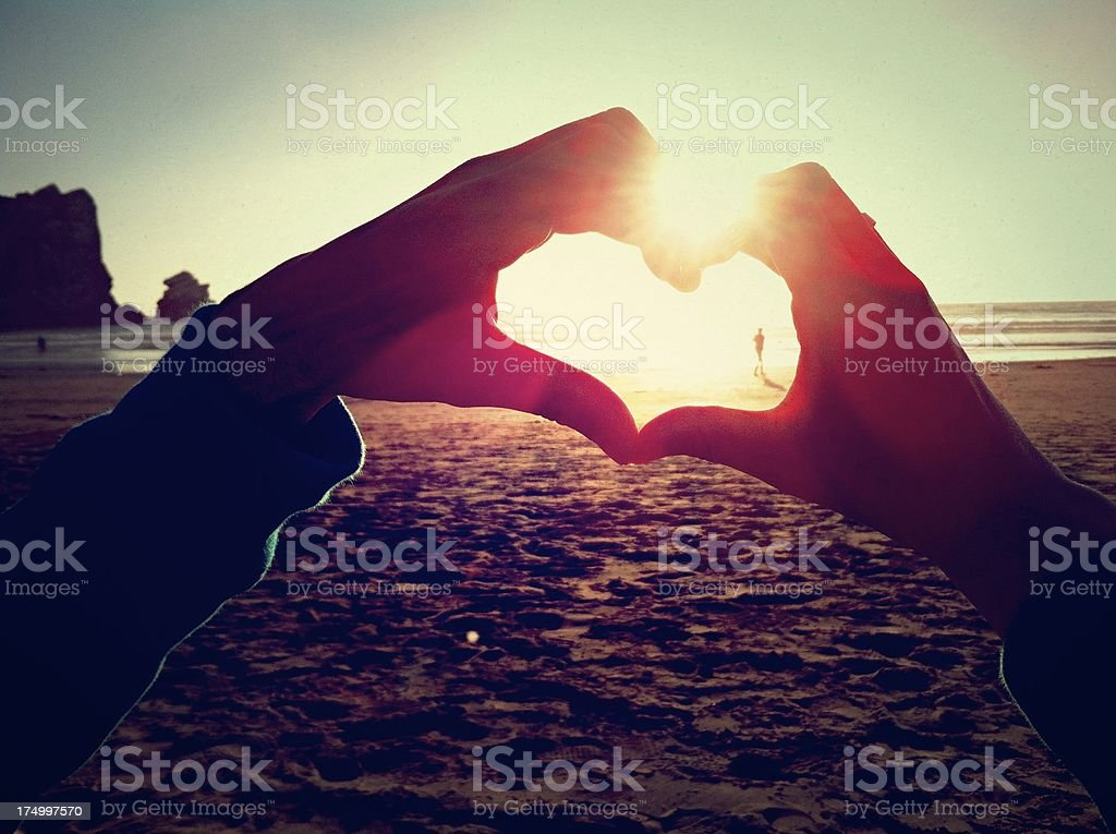 Heart symbol made with two hands on the beach stock photo