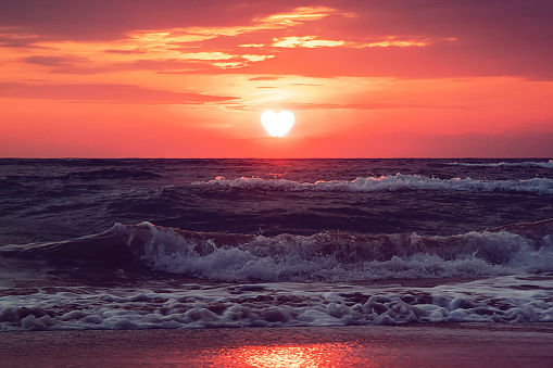 Heart walks off into the sunset over the sea in dark clouds. Past love. Separation. concept. Sun is the heart is the evening before sunset. Valentine's day