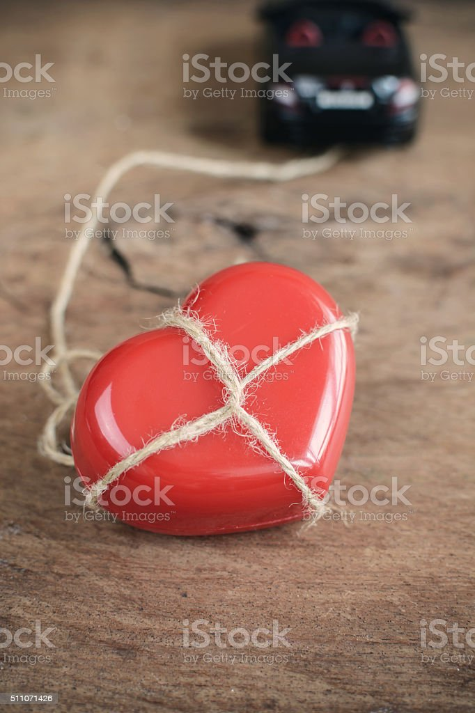 Heart which tied up with rope is towing by car stock photo