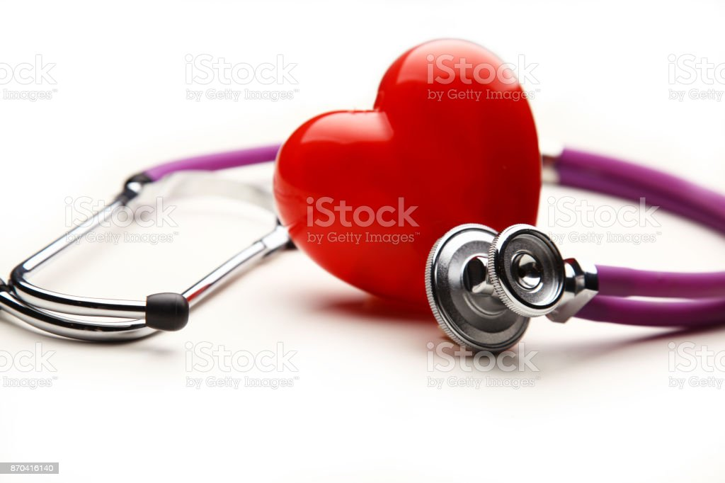 Heart with a medical stethoscope, isolated on wooden background stock photo