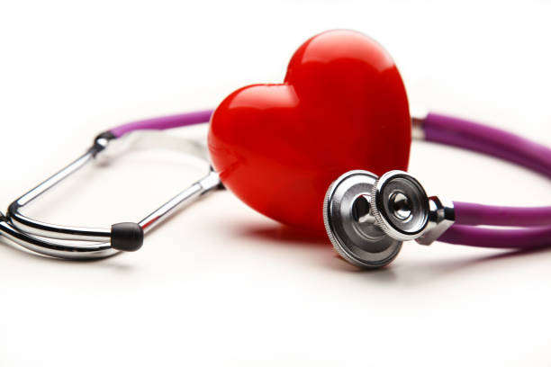 heart with a medical stethoscope, isolated on wooden background - heart internal organ stock photos and pictures