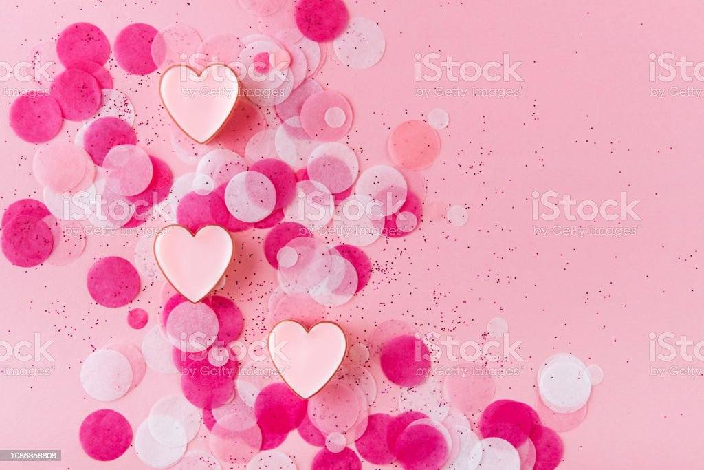 heart with confetti on pink background stock photo