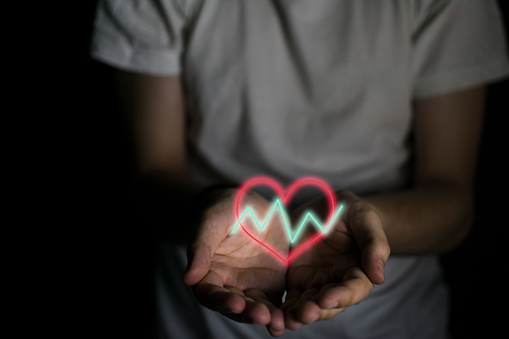 istock Heart with fluctuating lines on a man's hands 1163796321