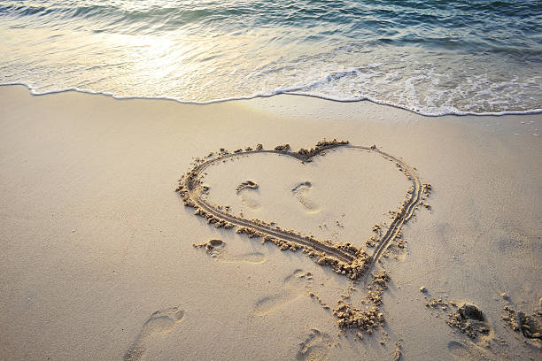 Heart with footprints drawn in the sand stock photo