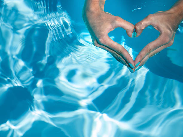 heart with hands in turquoise water heart with hands in turquoise water wading stock pictures, royalty-free photos & images
