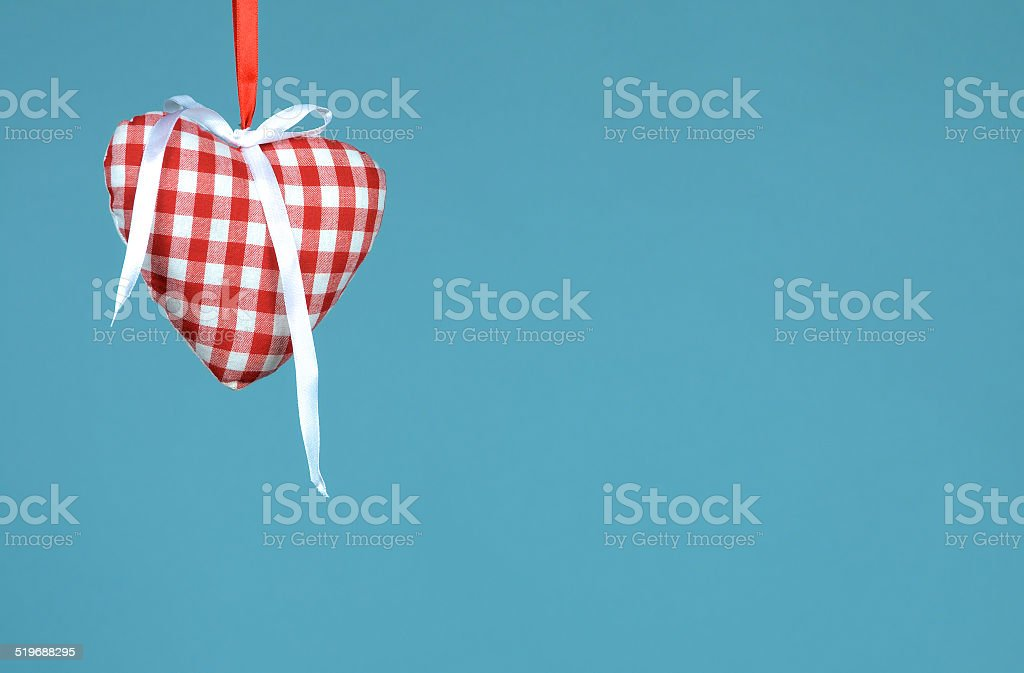 Heart with ribbon hanging against blue background stock photo