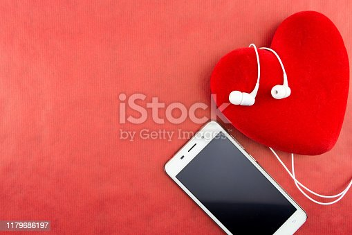 Heart with smartphone and earphones closeup on red with copy-space