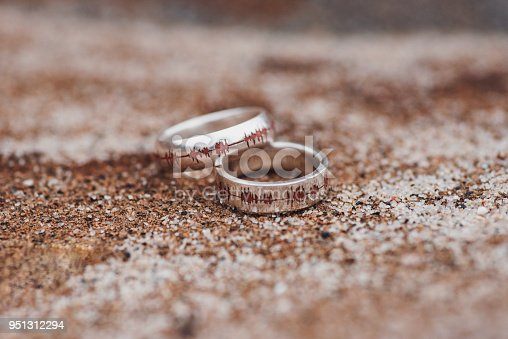 Heartbeat white gold wedding bands on sand
