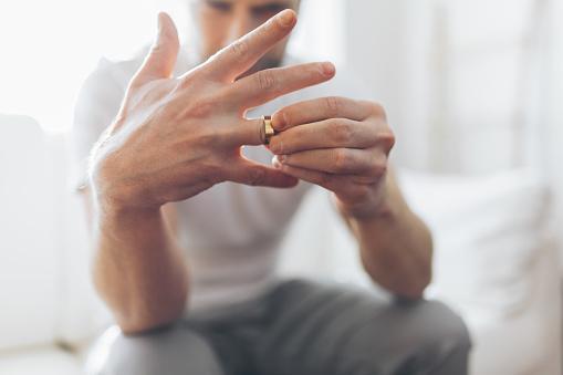 istock Heartbroken man holding a wedding ring 1134246406