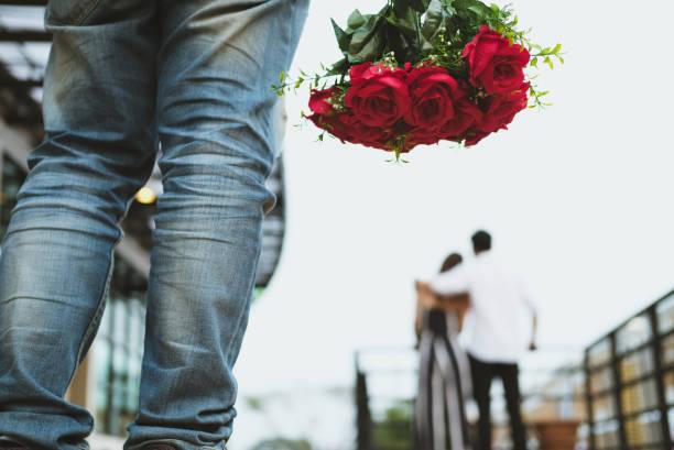 mit gebrochenem Herzen Mann, der Strauß roter Rosen traurig während sehen Frau dating mit einem anderen Mann hält. gebrochenes Herz in Liebe Konzept – Foto