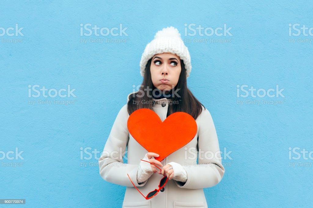 Heartbroken Sad Upset Girl Holding a Heart on Blue Background stock photo