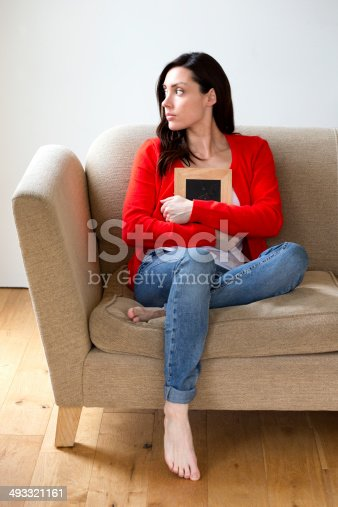 Young woman looking distraught and holding a photoframe